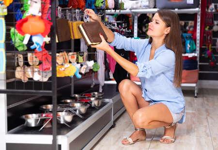 Young woman choosing accessories in petshop Stockfoto