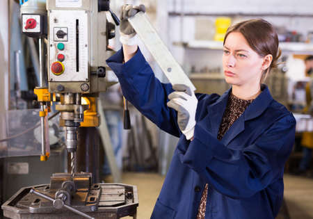 Female working on drilling machine