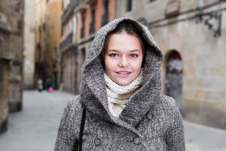 young girl in coat hood at the old street