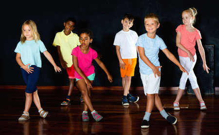 Group of smiling little boys and beautiful girls having dancing class in studio in the evening
