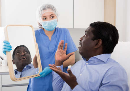 Indignant man looking at mirror after cosmetology procedures in clinic Stock Photo