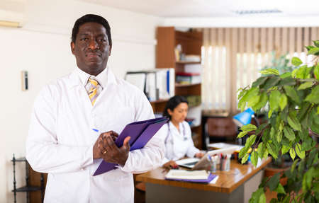 Positive african american physician filling out medical form at clipboard
