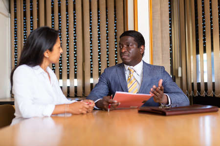 Businessman and businesswoman communicate and sign documents at the negotiation table in office