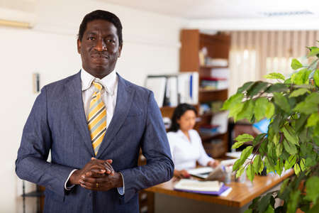 Successful african american businessman standing in office interior