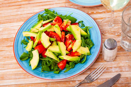 Tasty salad with avocado, tomatoe and arugula at plate Banque d'images