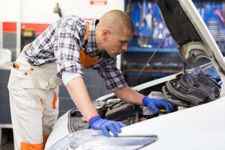 Positive man car mechanician repairing car in auto repair service