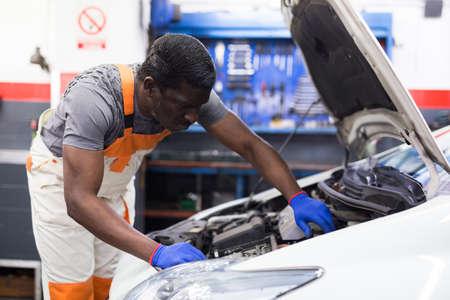Professional american mechanic man in uniform repairing car engine Stockfoto