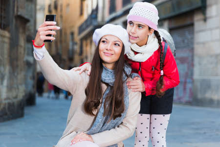 adult female and girl taking selfie