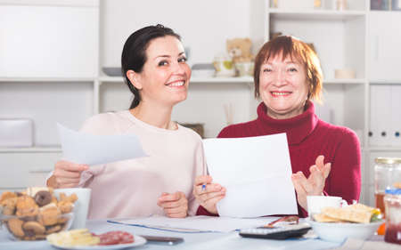 Portrait of mature woman and daughter with documents