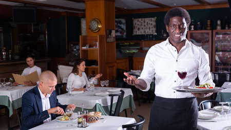 Hospitable african american waiter greeting guests in restaurant Archivio Fotografico