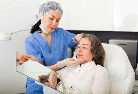 Cosmetologist consulting elderly woman before facial treatments Foto de archivo