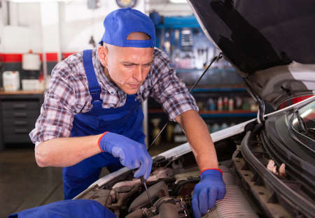 Car mechanic looking at open car hood for internal checking