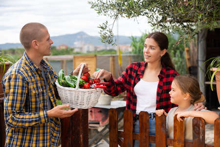 Young woman with daughter and man talking on the border of the garden plot