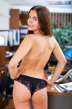 Back view of woman in black underwear in office