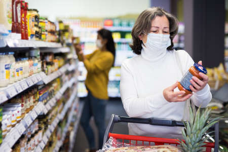 Mature woman in protective mask choosing food products on shelves in shop 免版税图像