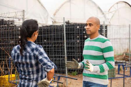 Latino man and woman talking near greenhouse