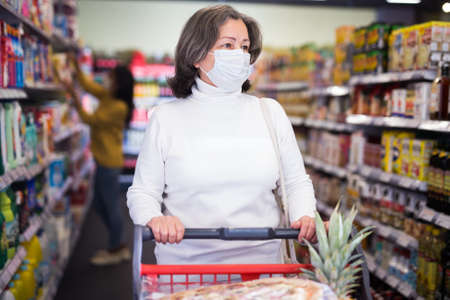 Aged woman in protective mask shopping at food section of supermarket