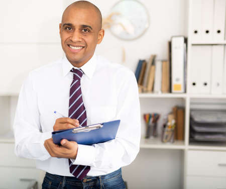 Cheerful business man in light shirt posing in office holding clipboard