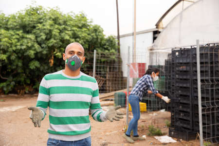 Portrait of farmer wearing protective mask in the backyard of house 免版税图像