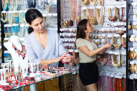 Young adult woman choosing jewelry in store 免版税图像