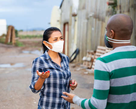 Male and female farmers in protective masks discussing outdoors 免版税图像