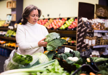 Mature woman choice cabbage on grocery store shelves