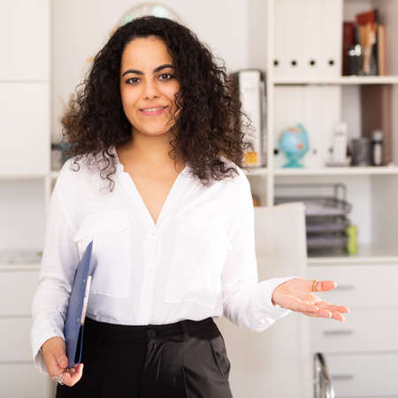 Businesswoman holding clipboard and welcoming to modern office 免版税图像