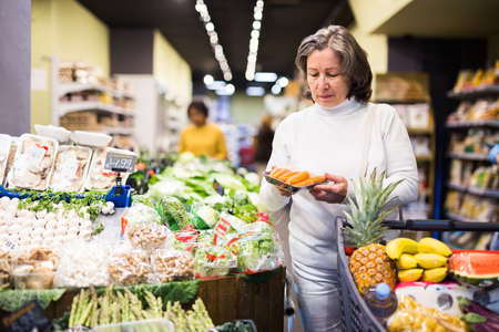 Interested aged woman choosing fresh carrots in supermarket