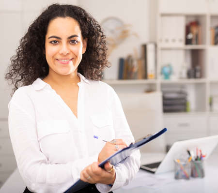 Young businesswoman with clipboard politely welcoming to company office