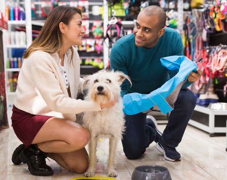 Happy married couple with dog in pet shop