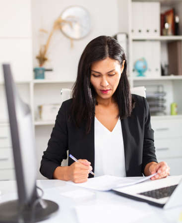 Young asian woman working in office and signs documents