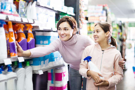 Woman with girl looking for cleaners in supermarket 免版税图像