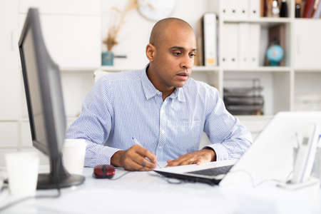 Professional business man using laptop at workplace
