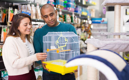 Man and woman choosing cage for bird