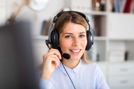 positive woman sitting with headphones in white room 免版税图像