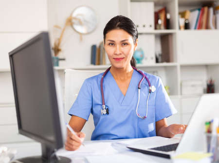Portrait of female doctor who is working with laptop and documents