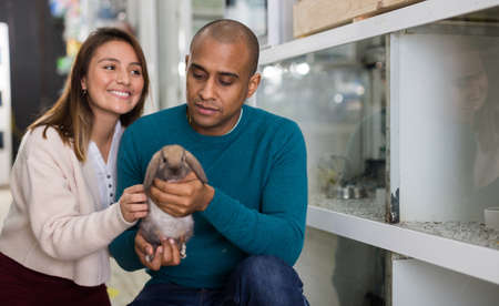 Family couple holding rabbit together in pet shop
