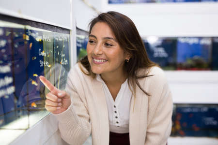 Portrait of interested young woman looking at colorful tropical fish in aquariums in shop