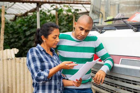 Man and woman farmers talking near car