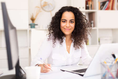 Young positive woman working at office