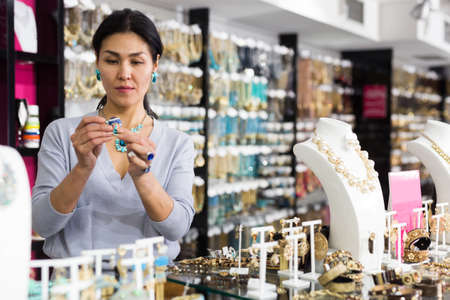 Smiling woman seller offering fashionable rings in jewelry store 免版税图像