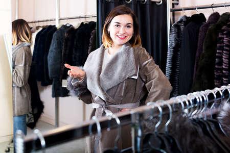 Female customer examining new sheepskin coat 免版税图像