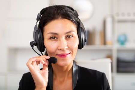 Portrait of woman call centre operator with headphones in office