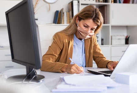 adult female manager in mask working during coronavirus 免版税图像