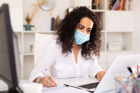 Woman in mask working at office