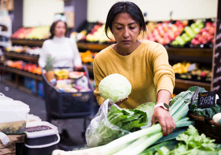 Ordinary woman buys cabbage at grocery supermarket