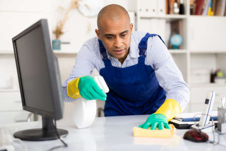 Man in an overalls cleans the table
