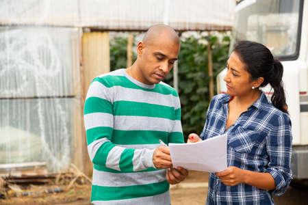 Woman and man discussing documents on farm near car 免版税图像