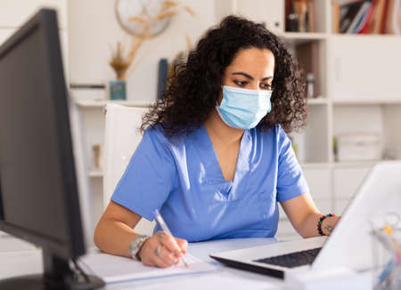 Doctor in mask working on laptop 免版税图像