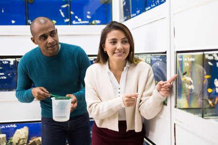 Positive salesman helping woman choosing aquarium fish
